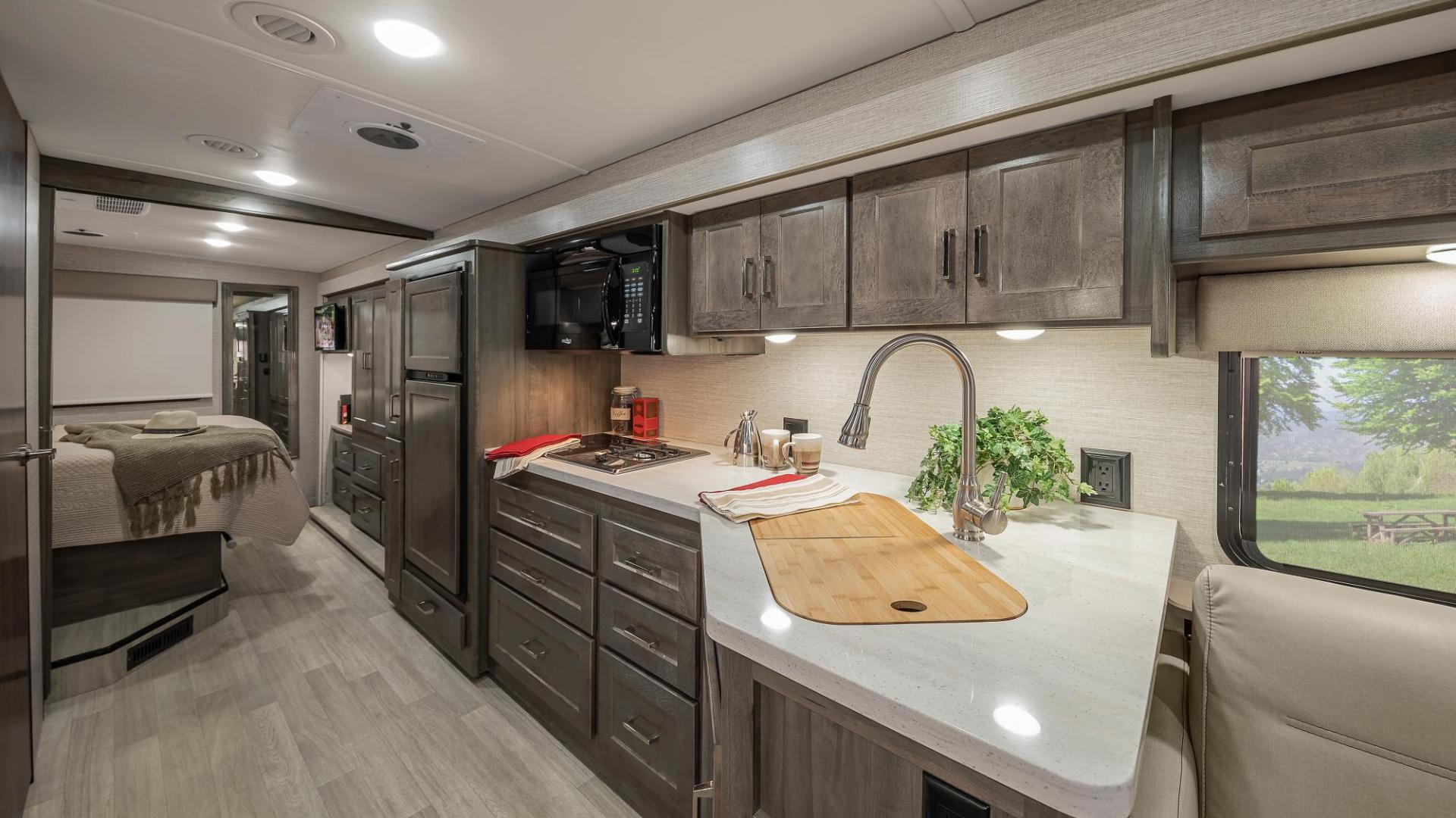 Full view of the Winnebago Adventurer Galley. Includes cabinetry, ample counterspace, and large sink.