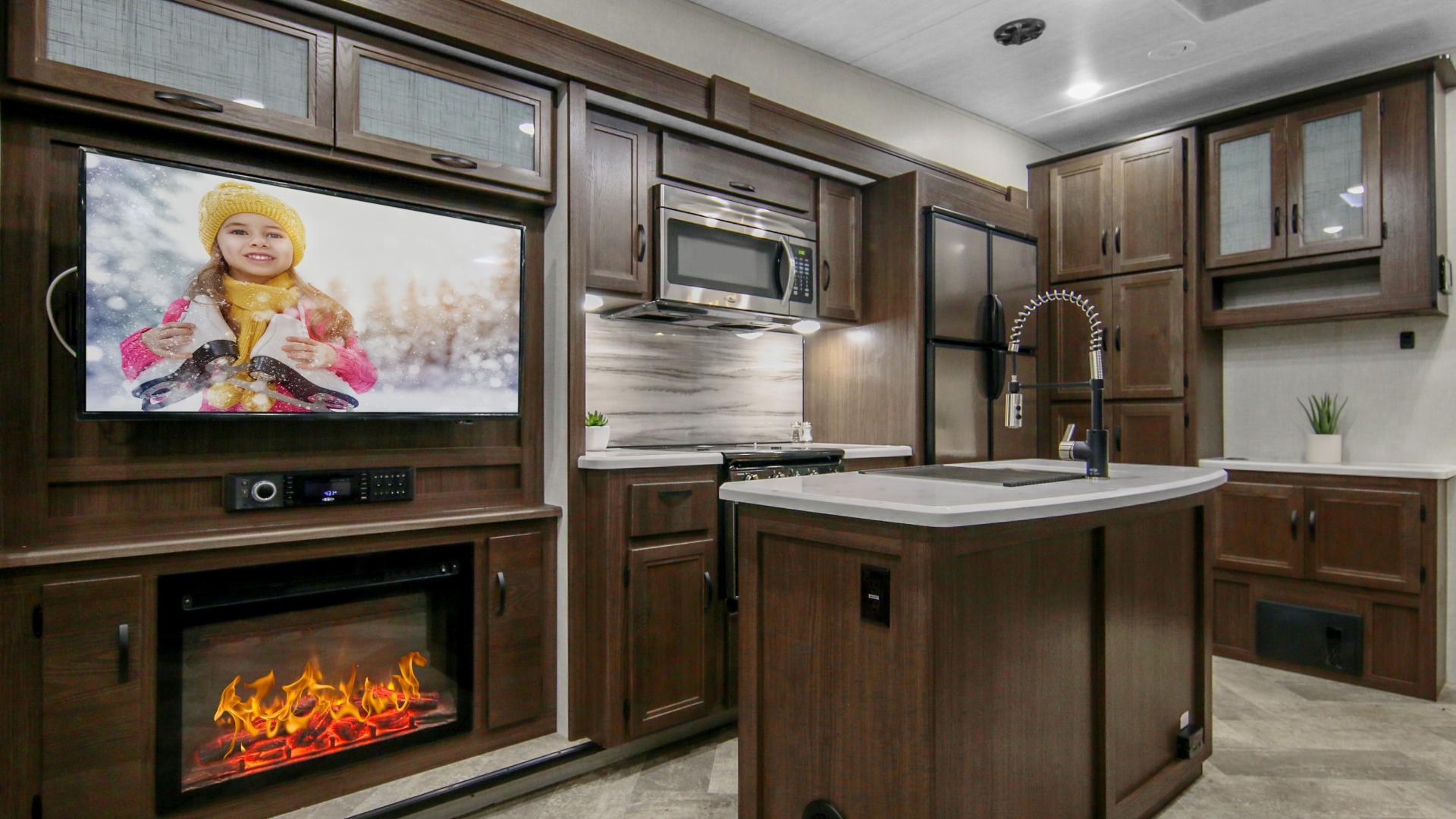 Winnebago Voyage Fifth Wheel kitchen area with island, tv enterntainment and fireplace