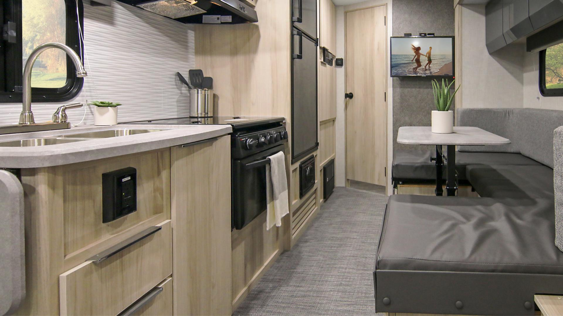 Winnebago Hike interior wide view of the living area, showcasing the galley, dinette and storage