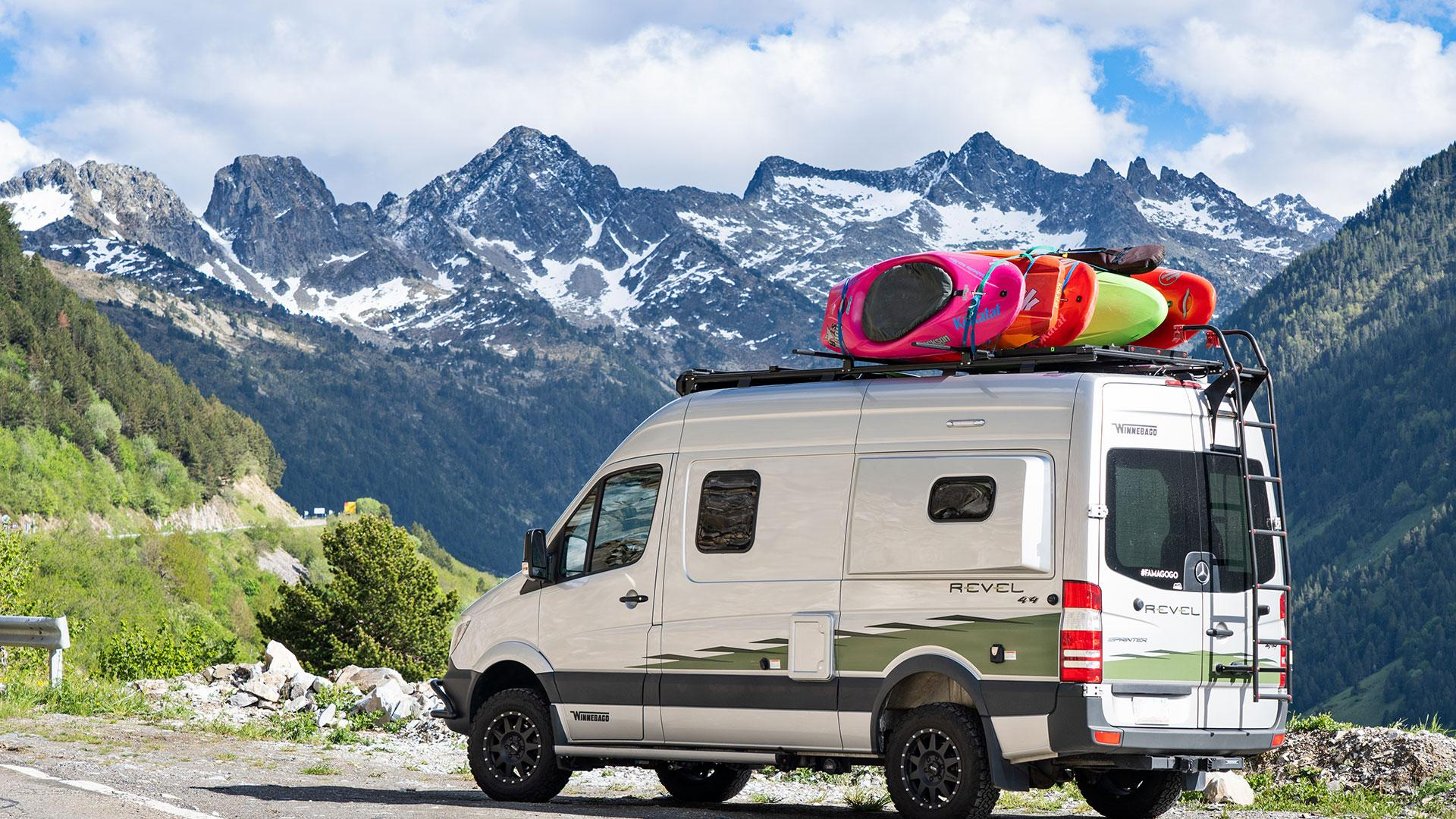Winnebago Revel with kayaks on roof rack parked on a mountain side