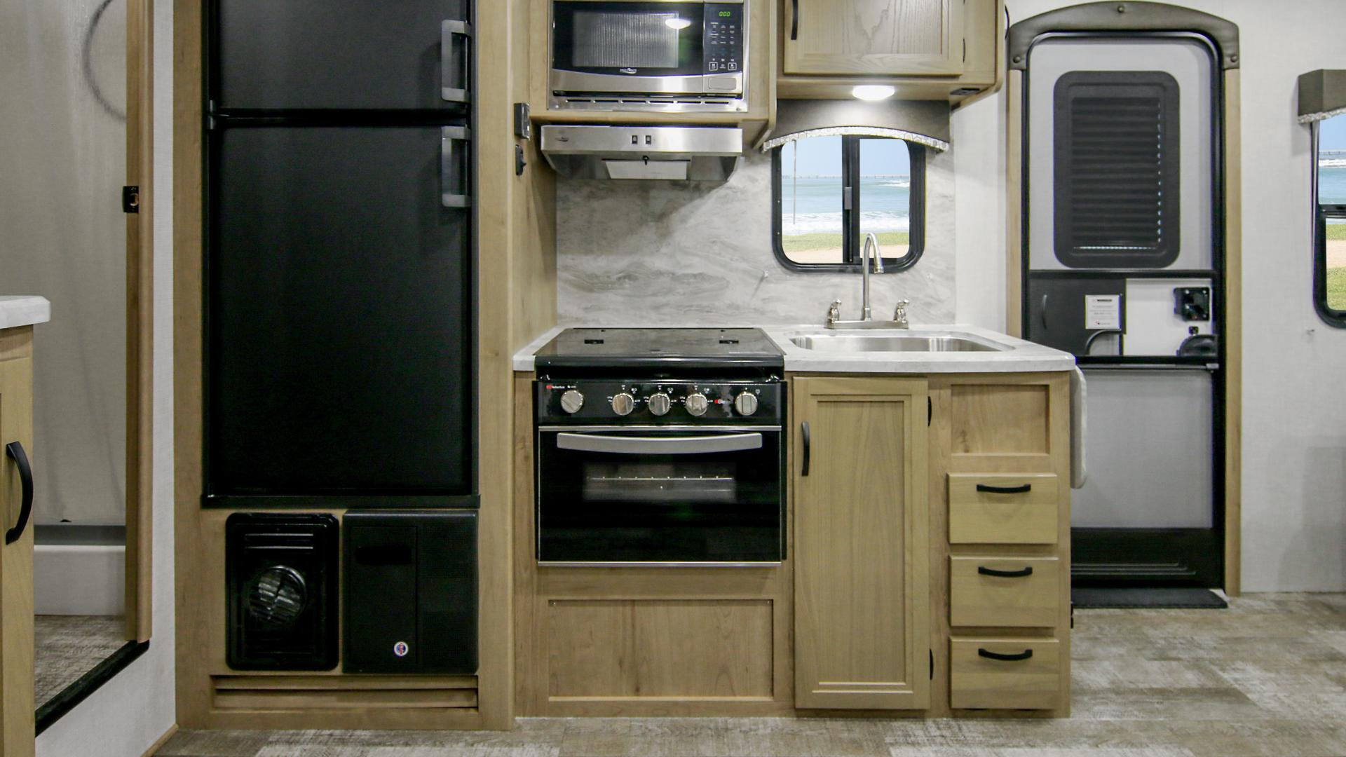 Micro Minnie Fifth Wheel 2405RL galley featuring a stove, oven, refrigerator and sink
