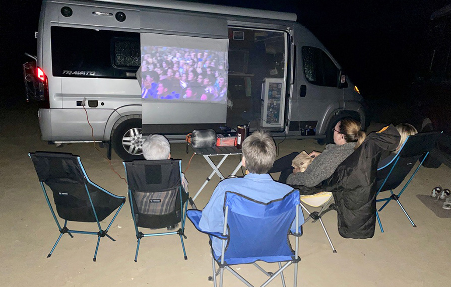 Group of people sitting in camp chairs watching a movie projected onto a sheet hanging on Travato