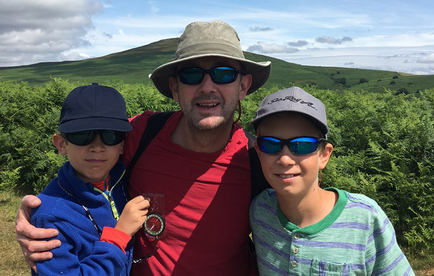 Huw Bower with kids smiling in front of green rolling hills