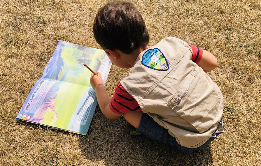 Caspian sitting on grass writing in the junior ranger booklet