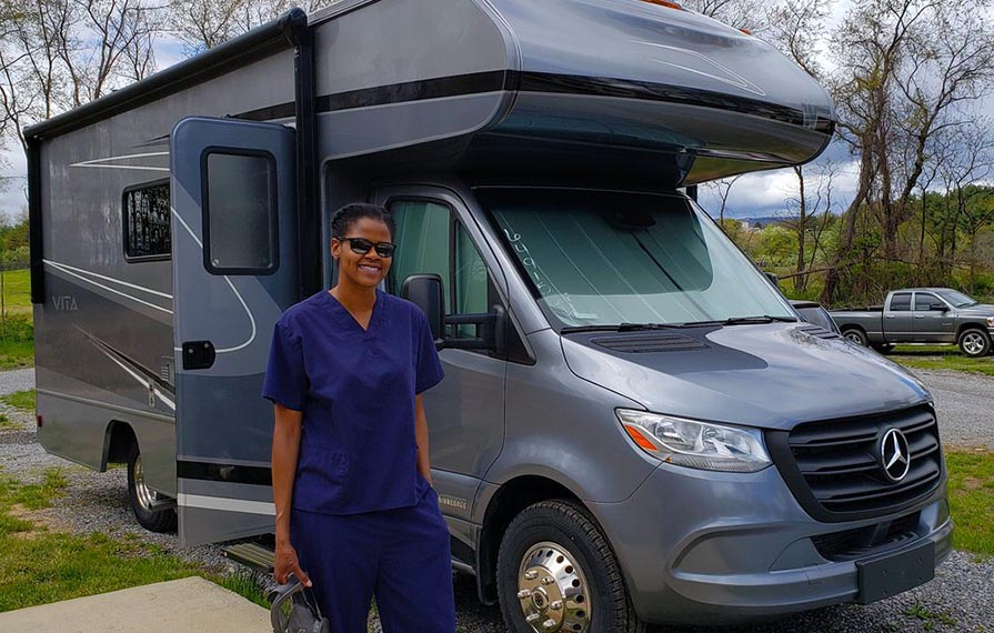 Sabrina wearing blue scrubs standing in front of Winnebago Vita