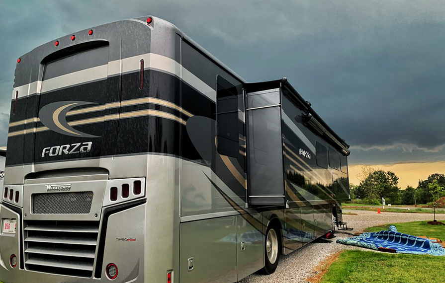 Forza parked on gravel with dark skies overhead