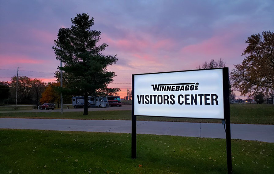 Winnebago Visitors Center sign with pink and purple sunset in background