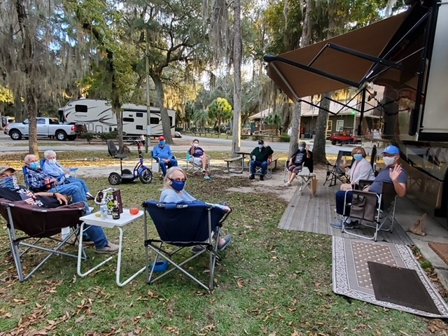 People sitting in camp chairs outside motorhomes.
