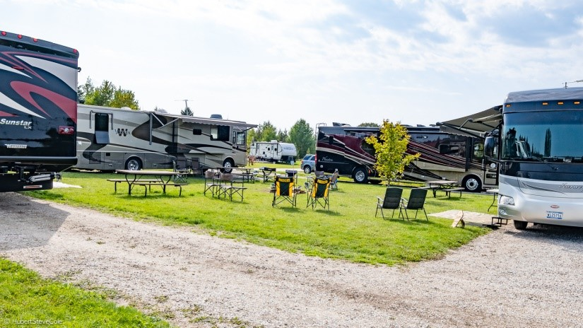 Four motorhomes parked with chairs and picnic tables on the lawn between them.
