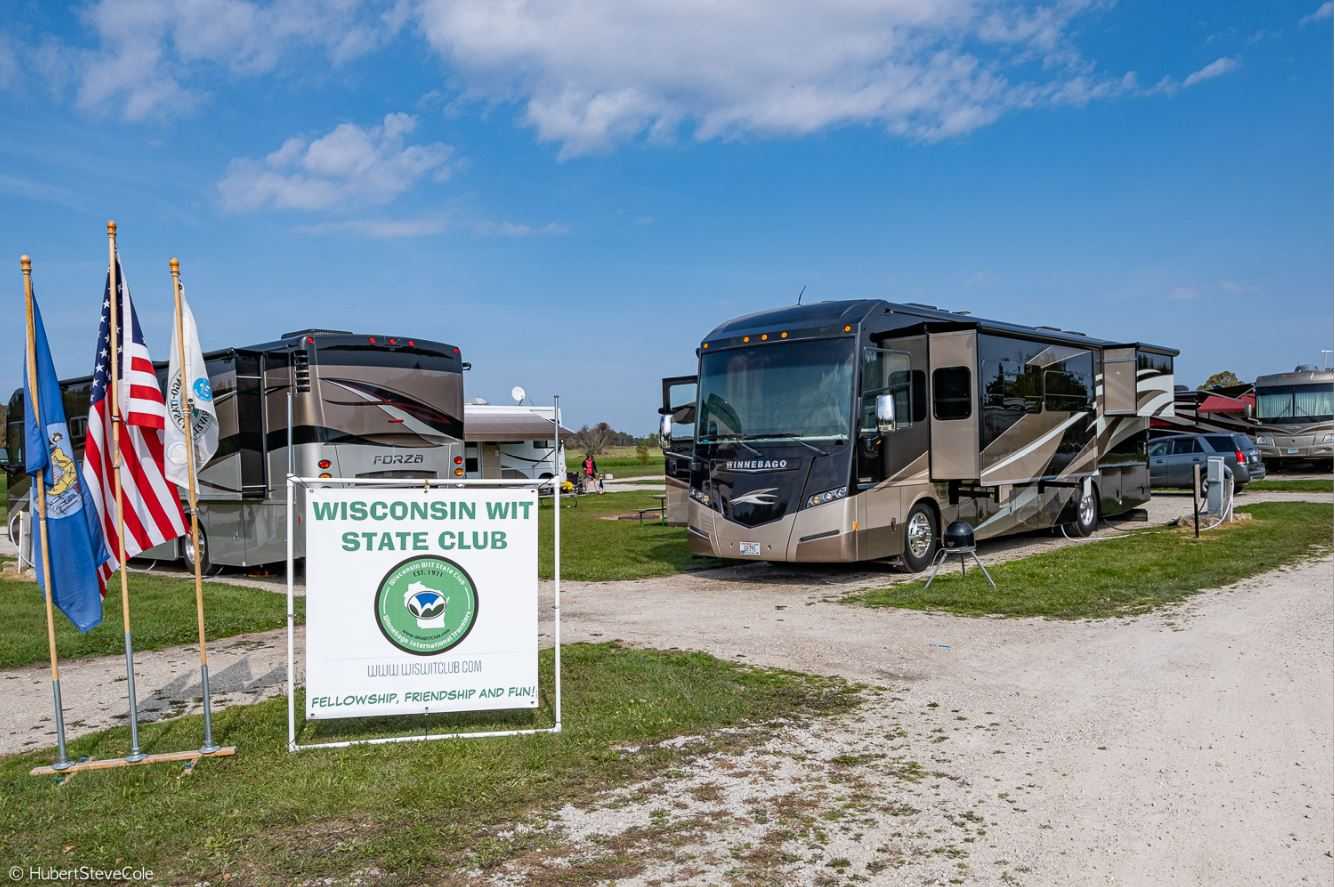 Two Winnebago motorhomes parked in campsites with Wisconsin WIT State Club Sign in the grass.