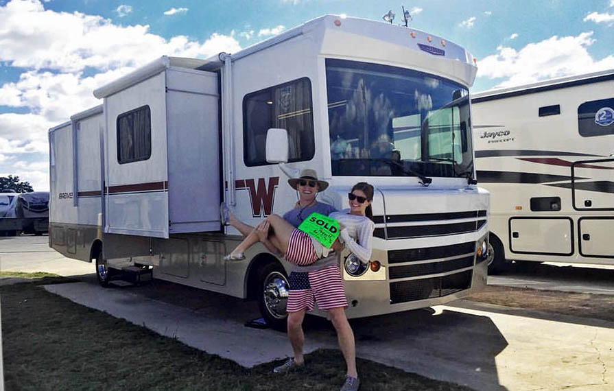 Heath holding Alyssa in front of Winnebago Brave with a bright green sold sign