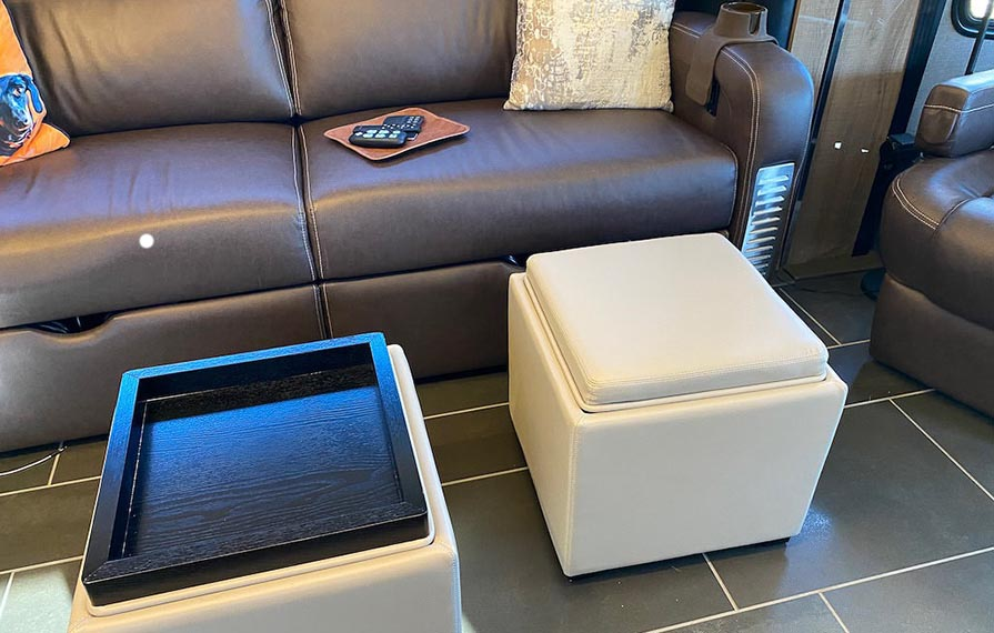 Two tan storage ottomans in front of brown sofa