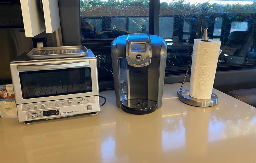 Toaster oven, coffee maker, and paper towel holder sitting on countertop