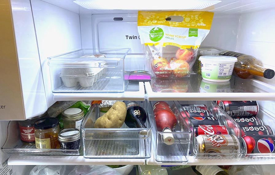 Refrigerator with dividers full of food and drinks