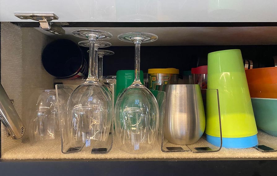 A cabinet full of cups and drinking glasses sitting between dividers
