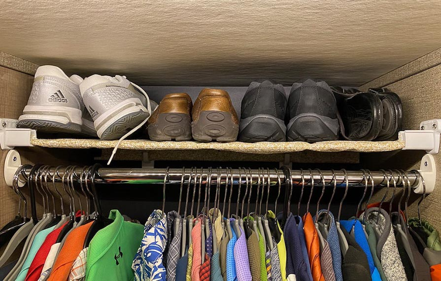 Shoes lined nicely on shelf above hanging clothes in closet