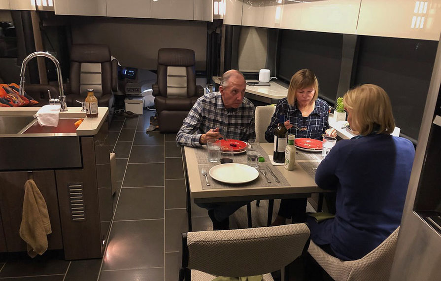 Three people eating at kitchen table
