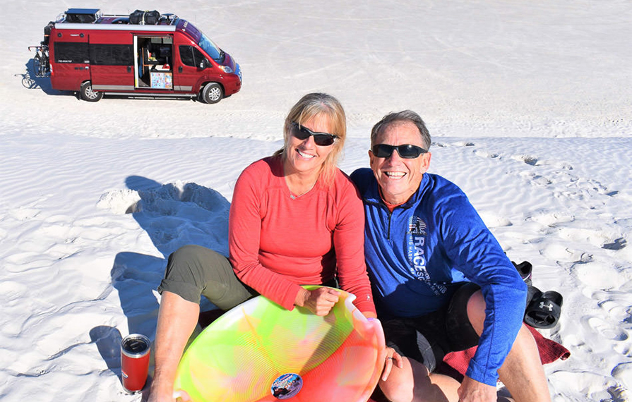 Jim and Rhonda Kohnke sitting in sand at White Sands National Park with red Travato behind them