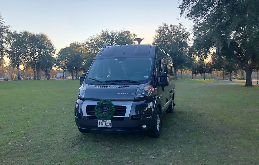 Travato parked on grass with a green wreath on front grill
