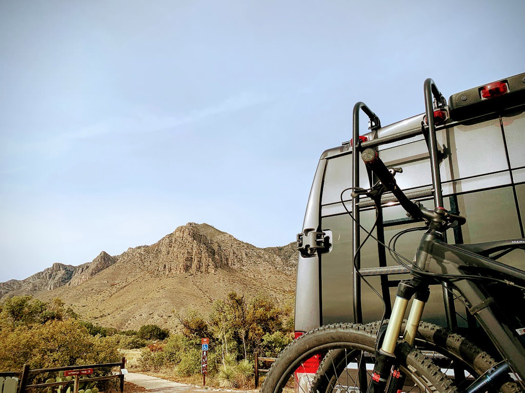 Back of Winnebago Limited Edition National Park Foundation Travato parked with the Guadalupe Mountains in the background