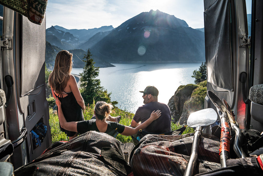 3 people sitting at the back of their Winnebago Revel looking out over a lake with mountains in the background.