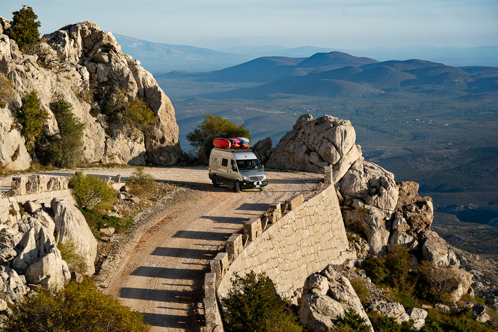 Winnebago Revel driving on rock surrounded high road in Croatia