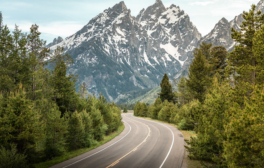 Mountains ahead and tress to the right and left on Tetons Scenic Road