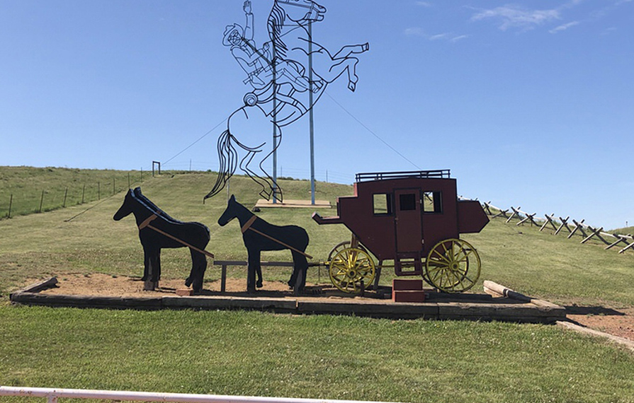 Teddy Rides Again sculptures. One sculpture is a stagecoach and the other of Roosevelt on his horse.