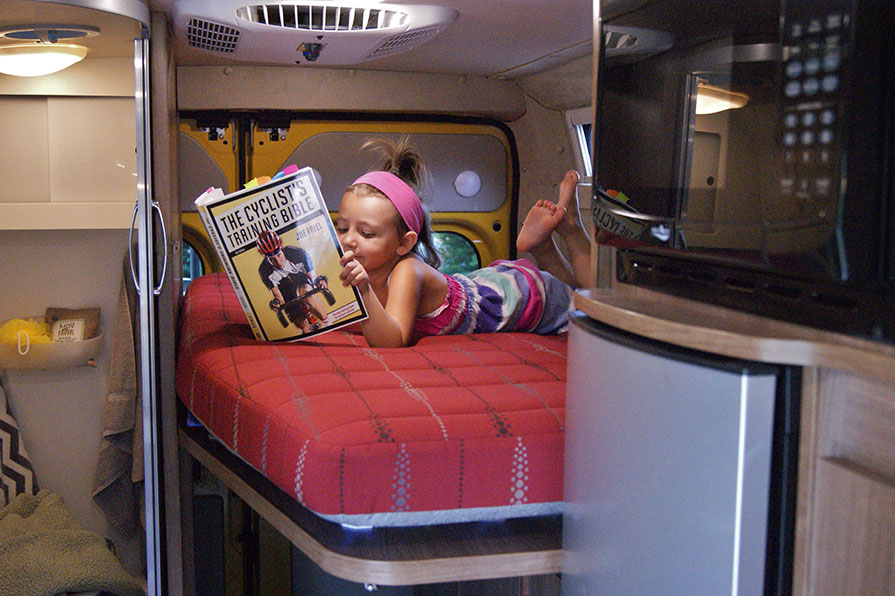 Little girl reading a book on back bed of a RV.