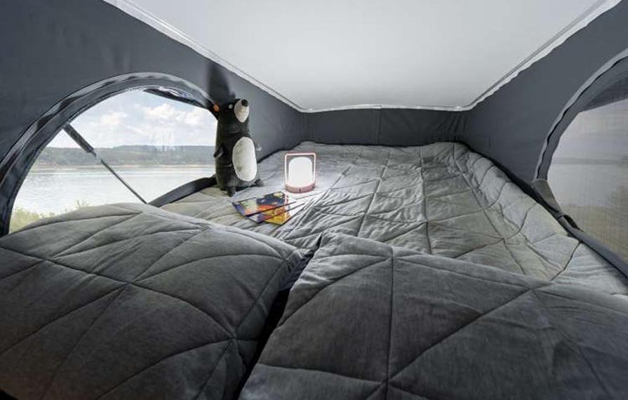 View of the Winnebago Solis pop-top bed with a lantern and stuffed animal on it.