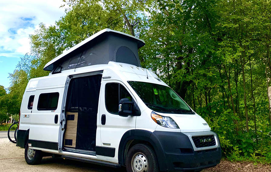 Winnebago Solis parked near trees with pop-top up