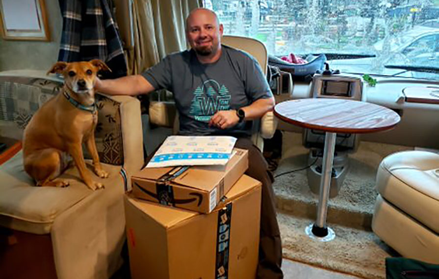 Kenny and Bella sitting inside Vista near a stack of Amazon packages