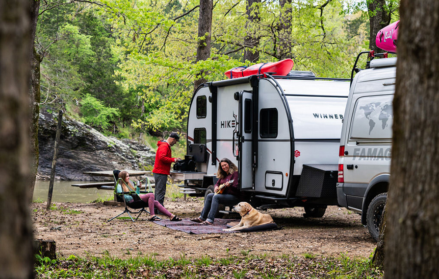 Holcombe family sitting outside of their Winnebago Hike with their dog Tucker