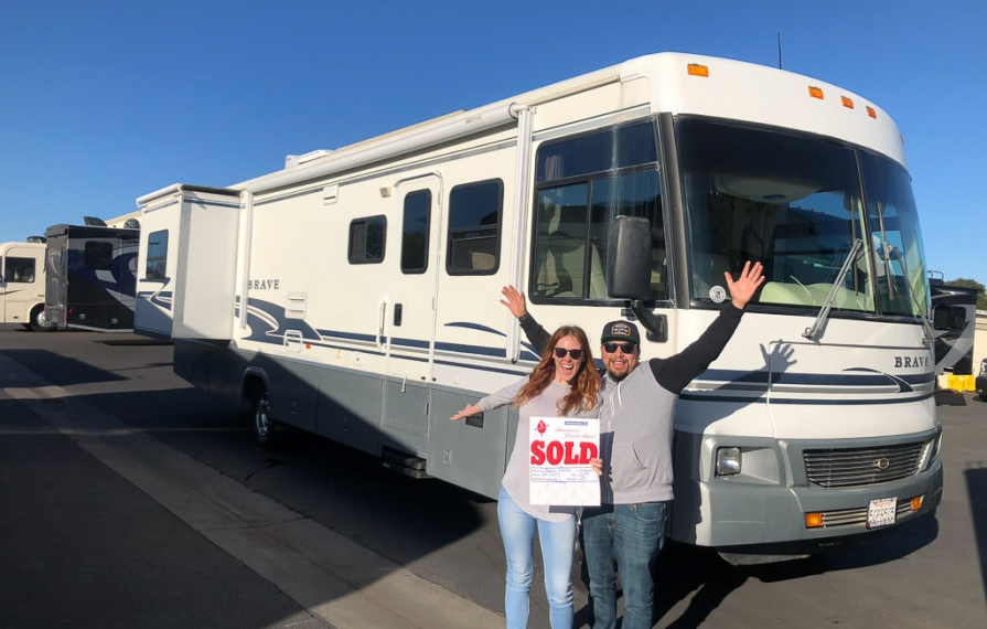 Ashley and Jessie holding sold sign standing in front of Winnebago Brave