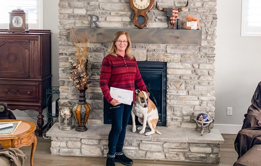 Family member holding stack of mail - standing next to white and tan dog in front of fireplace