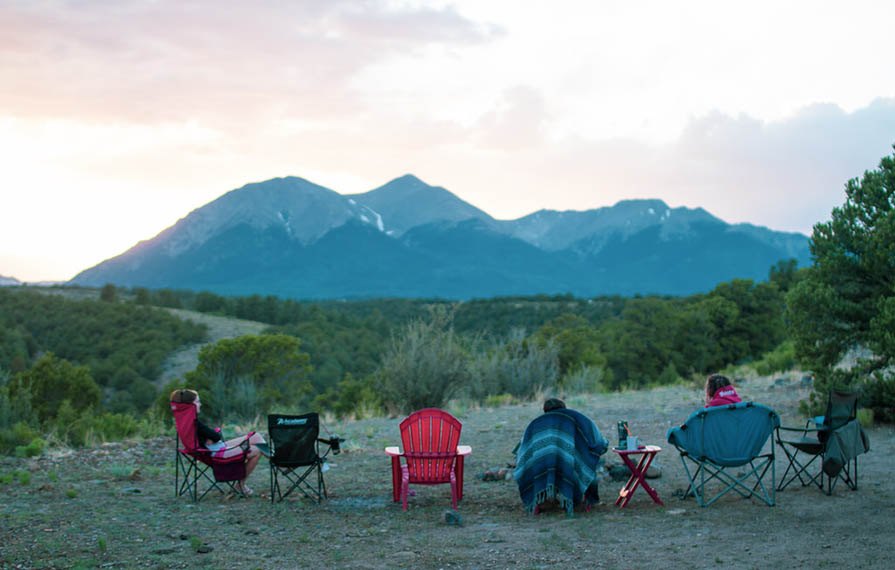 Shot from behind of three friends sitting in camp chairs looking at mountain view