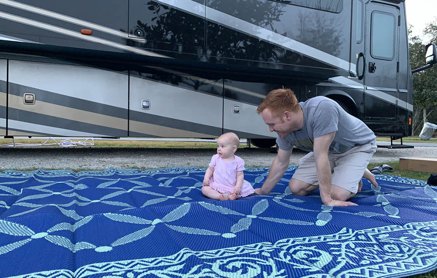 Heath and Ellie sitting on outdoor rug outside of RV