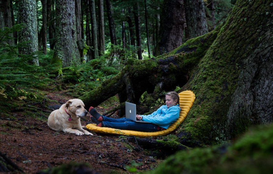 Abby sitting on inflatable mattress next to tree working on laptop with Tucker the dog at her feet.