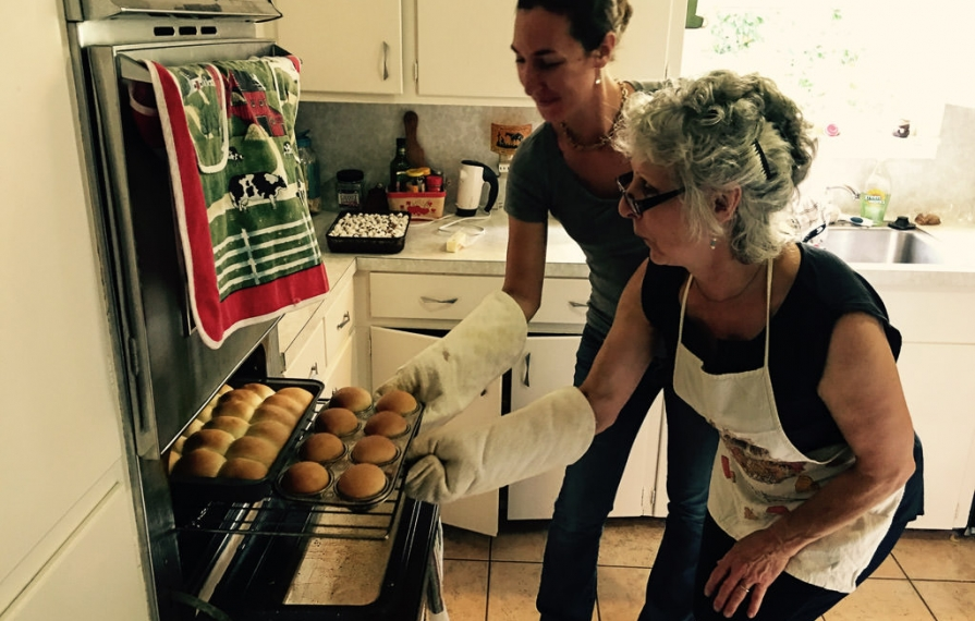 Brittany and her mom taking rolls out of oven