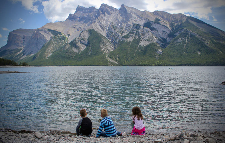 Three kids sitting next to Lake Minnewanka