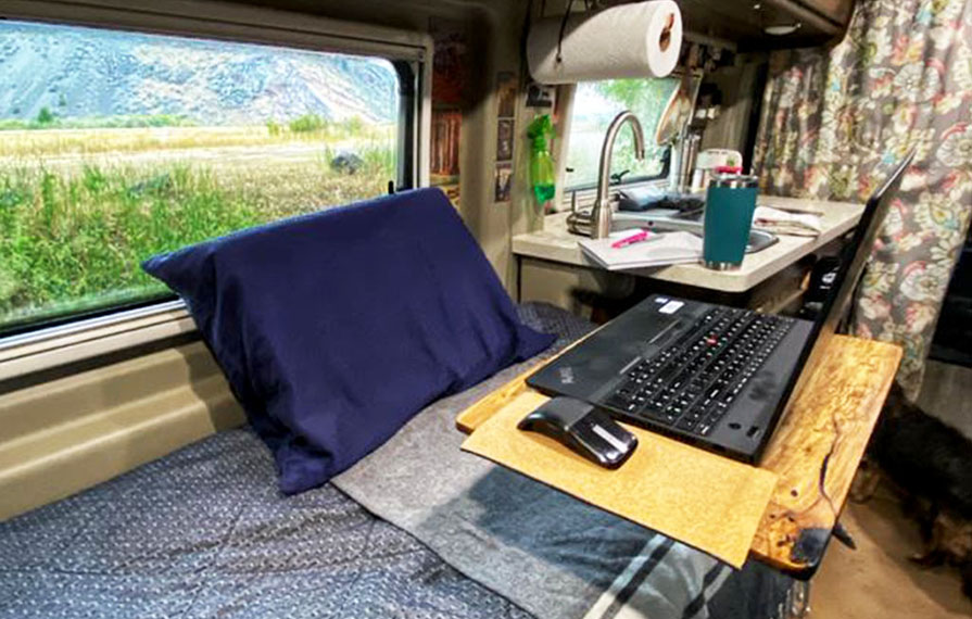 Wooden desk with laptop on it over Travato bed