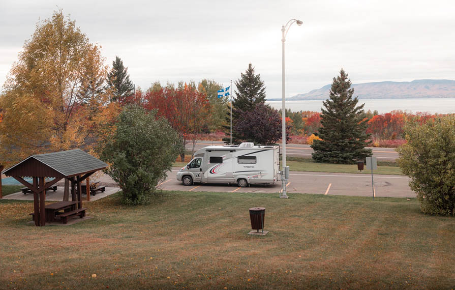 Trend parked in parking lot near pic table. Red fall trees in background.