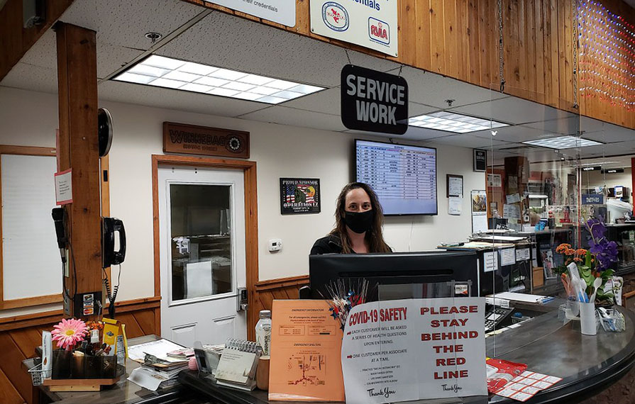 Winnebago employee wearing mask standing behind front desk
