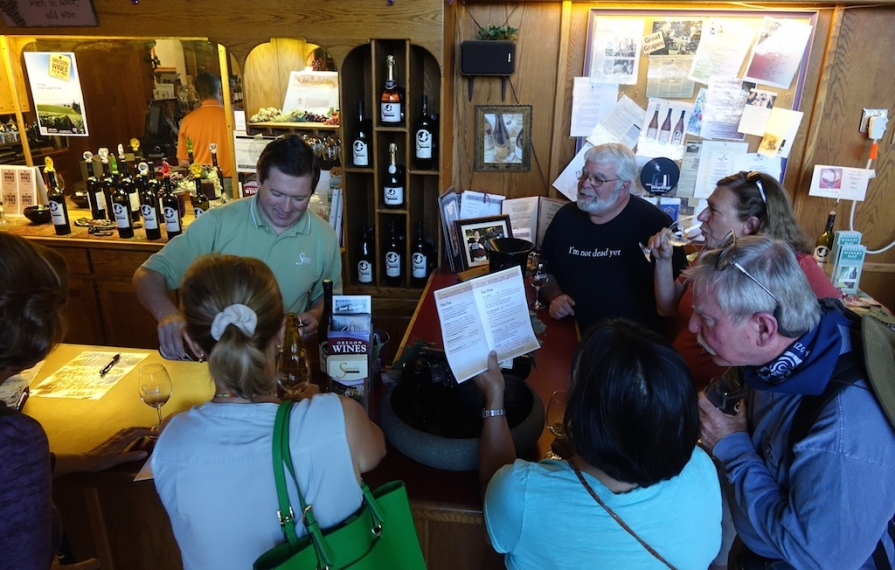 A group gathered at a bar for a wine tasting.