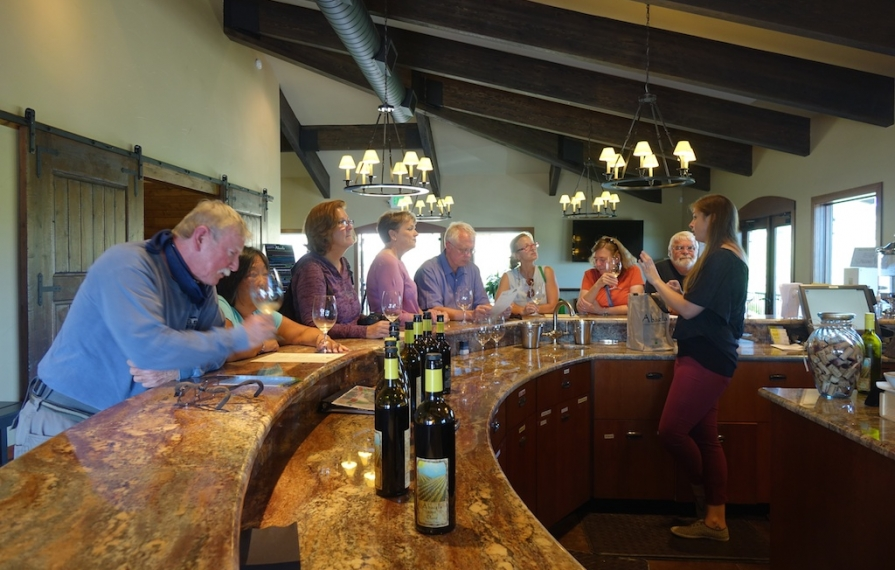 Group of people standing along a bar for a wine tasting.
