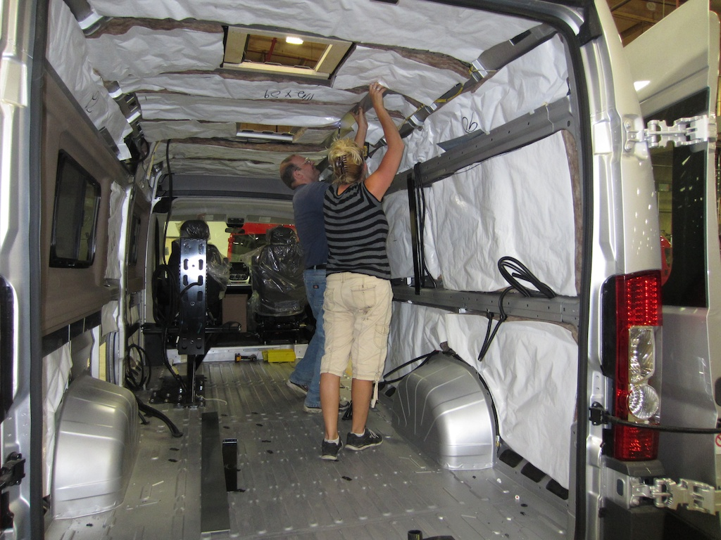 Two people adding insulation to a Winnebago Travato.