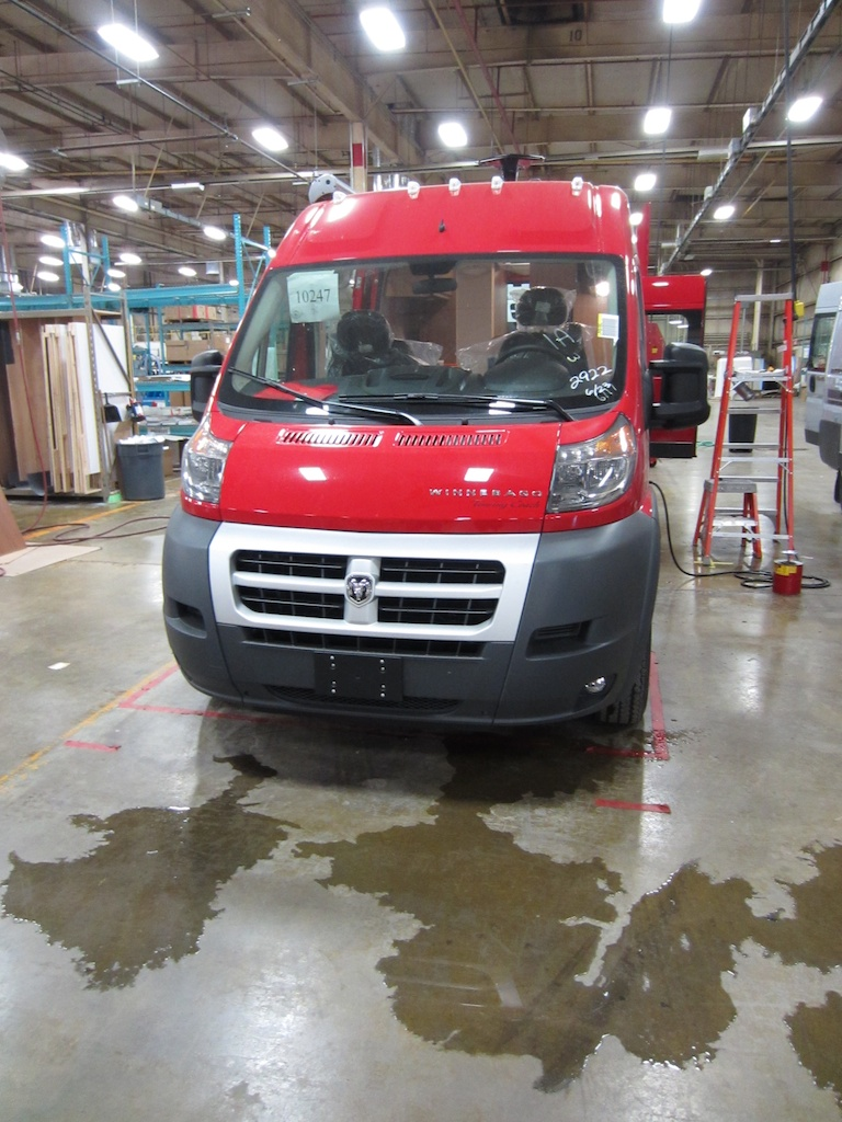 Red Winnebago Travato being water leak tested.