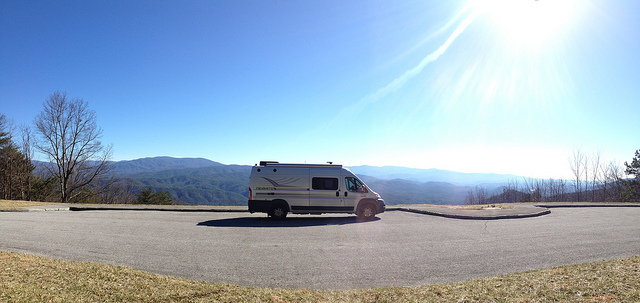 Winnebago Travato parked with mountains in the distance.