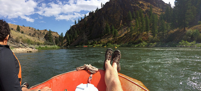 Feet up on the edge of a raft with water and mountains surrounding