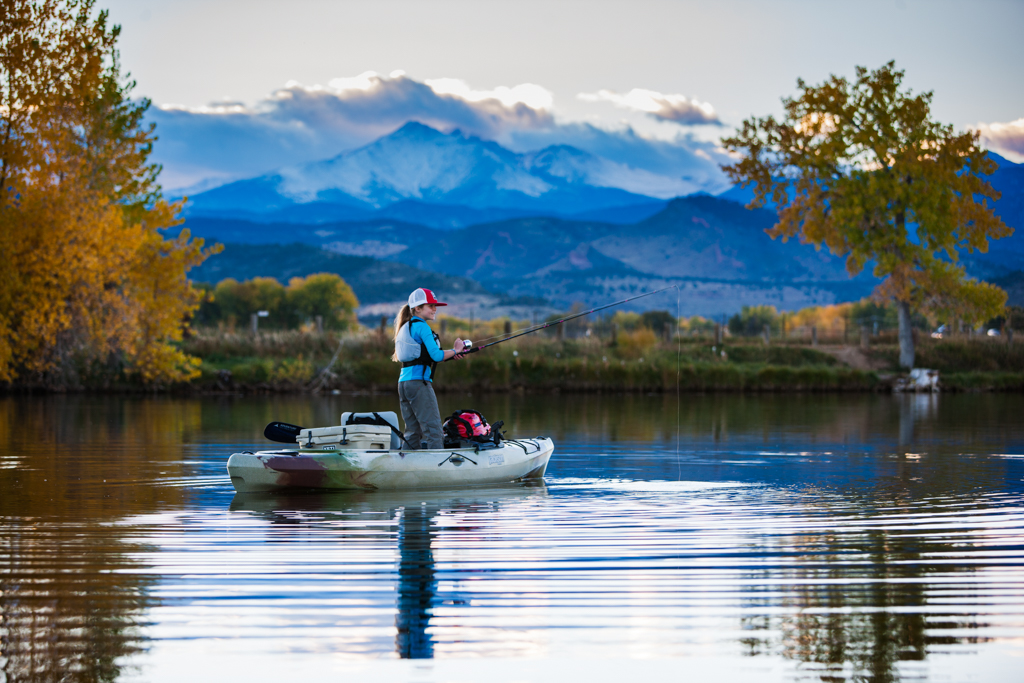Abby kayak fishing with mountains in the background.